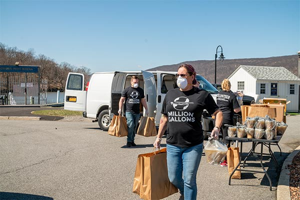 volunteers deliver bags of soup at pickup location
